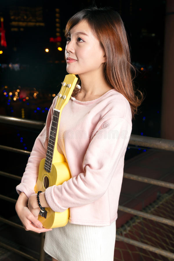 Pretty Asian woman with ukelele stock images