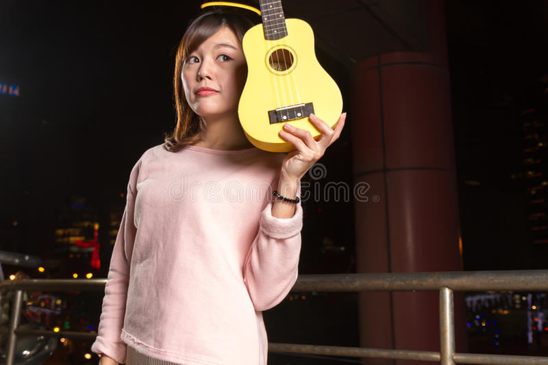 Pretty Asian woman with ukelele royalty free stock image