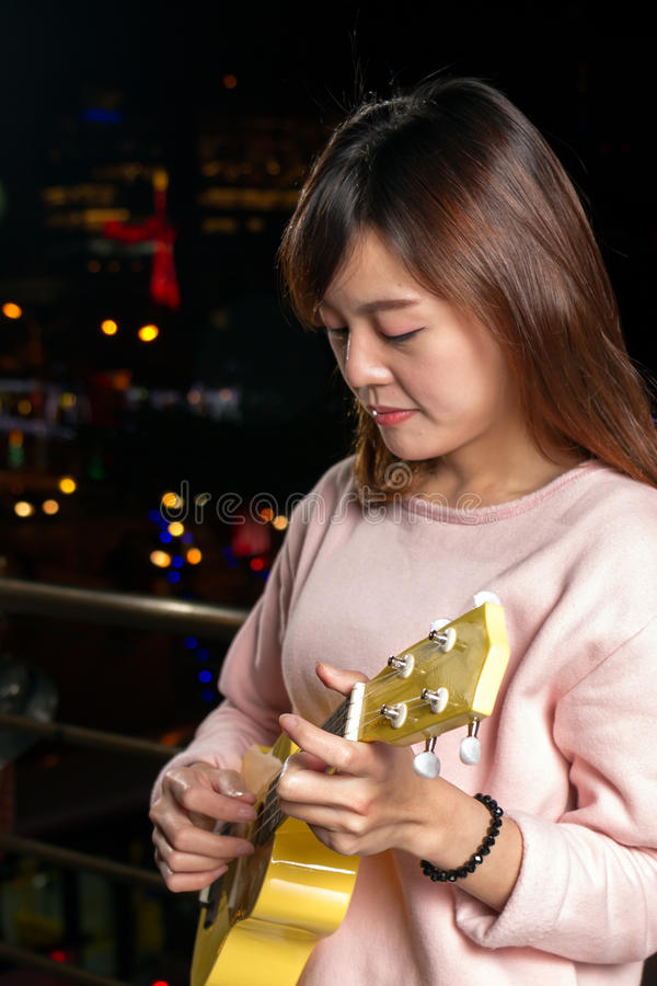 Pretty Asian woman with ukelele stock photography