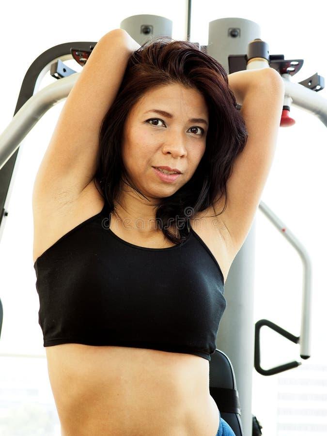 Pretty woman using an exercise machine stock photo