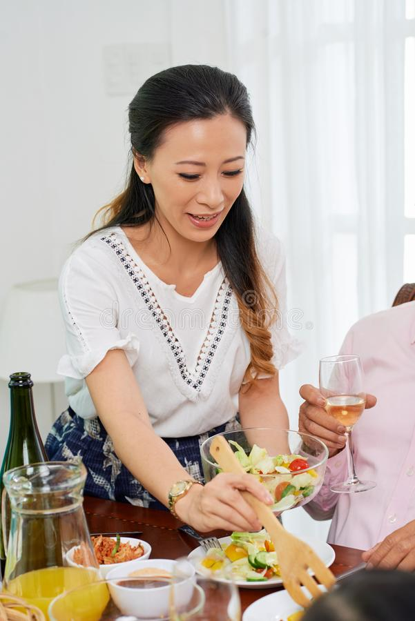 Beautiful woman serving meal for family royalty free stock photo