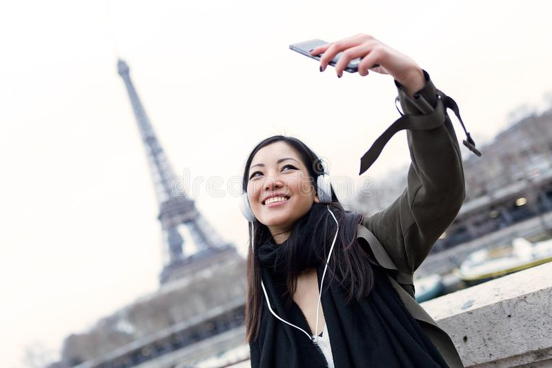 Pretty asian young woman taking a selfie in front of Eiffel tower in Paris while listening to music. stock photos
