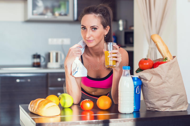 Pretty attractive athletic active sportive lady. Woman standing in kitchen with a towel on her shoulder and healthy food fresh fruits milk bread drinking juice stock photography