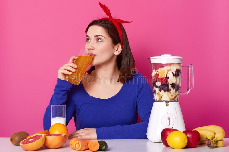 Pretty attractive woman with red headband on her head drinking fruit orange smoothie, looking up, holding glass. Brunette model royalty free stock photo