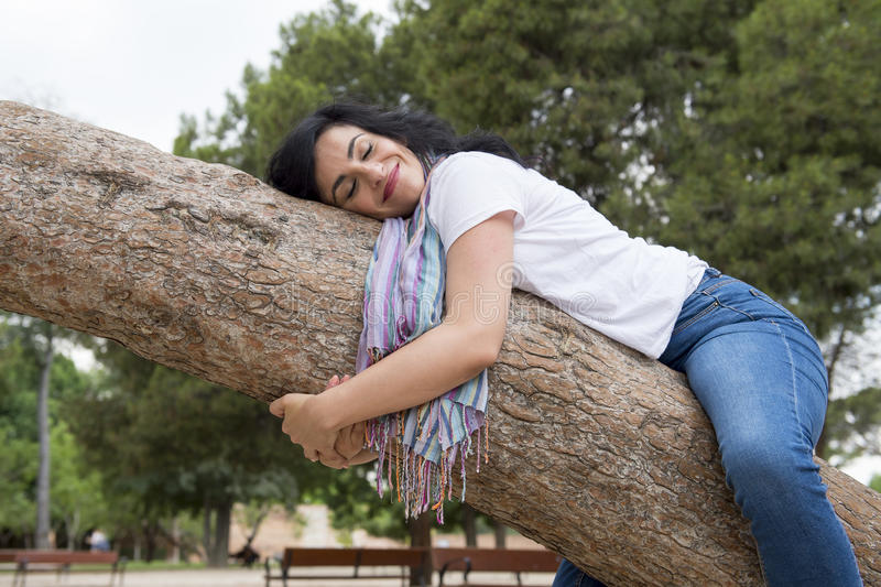 Pretty attractive woman wearing causal clothes and hugging a tree in a green park stock images