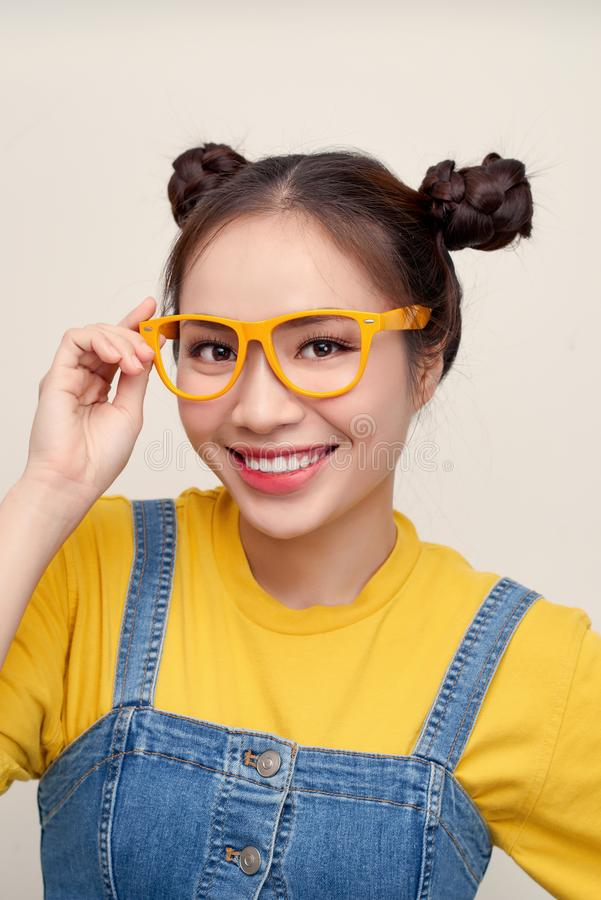 Pretty attractive young Asian woman holding her glasses with two hair-buns royalty free stock photography