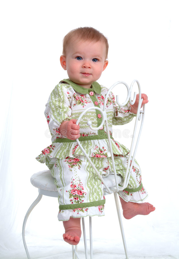 Pretty Baby. Baby girl sitting on a chair backwards holding back of chair royalty free stock photo