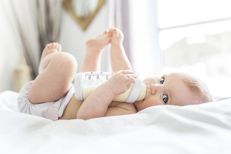 Pretty baby girl drinks water from bottle lying on bed. Child weared diaper in nursery room. royalty free stock photography
