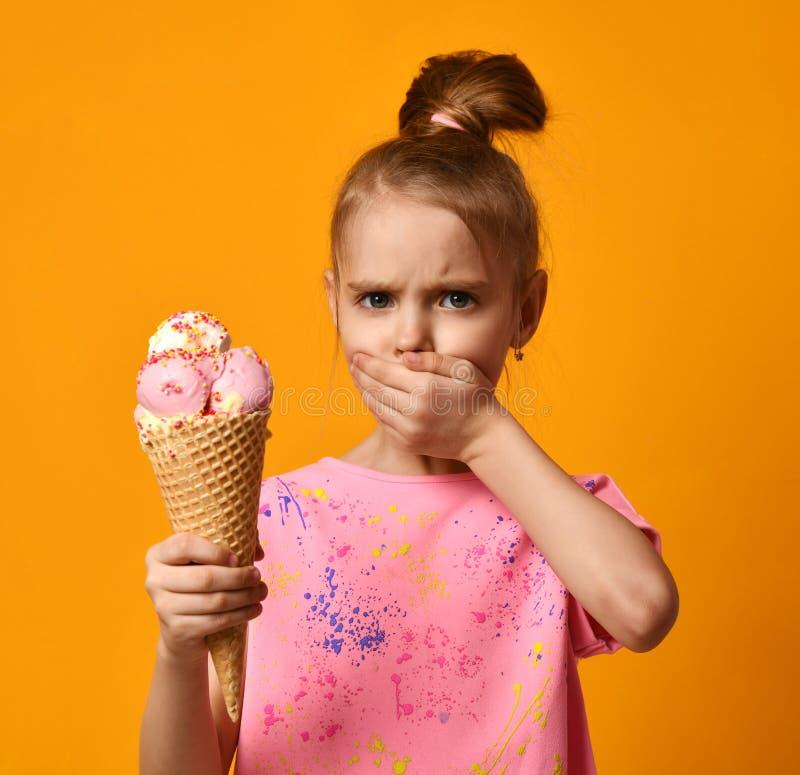 Pretty baby girl kid eating licking banana and strawberry ice cream in waffles cone stock photo