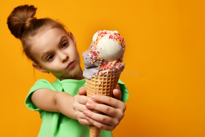 Pretty baby girl kid eating licking banana and strawberry ice cream in waffles cone stock image