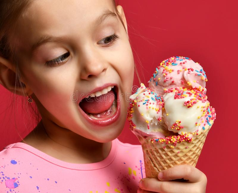 Pretty baby girl kid eating licking big ice cream in waffles cone with raspberry happy laughing royalty free stock photography