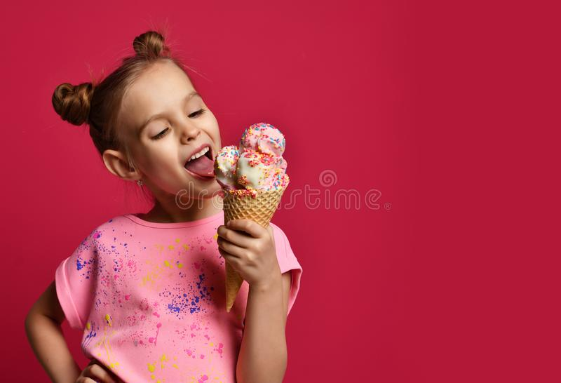 Pretty baby girl kid eating licking big ice cream in waffles cone with raspberry happy laughing royalty free stock images