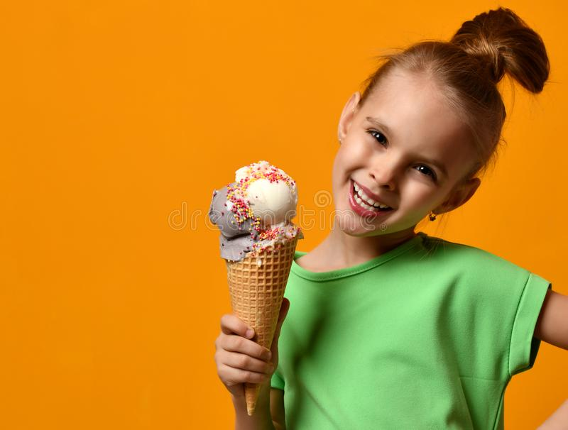 Pretty baby girl kid eating licking vanilla ice cream in waffles cone royalty free stock photography