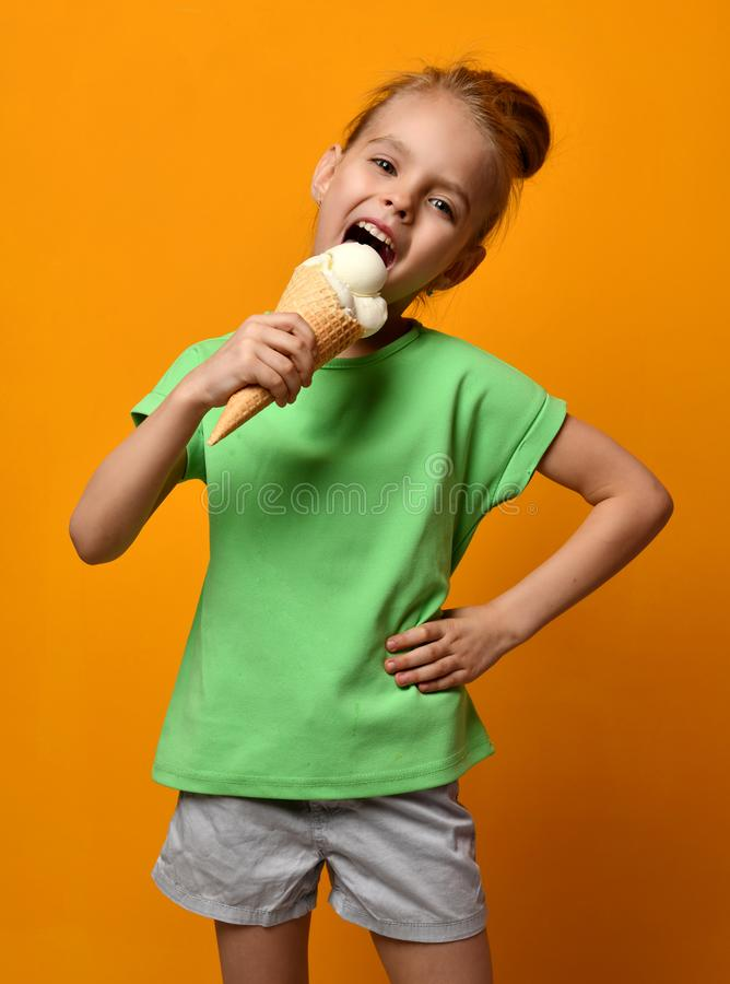 Pretty baby girl kid eating licking vanilla ice cream in waffles cone on yellow background stock photo