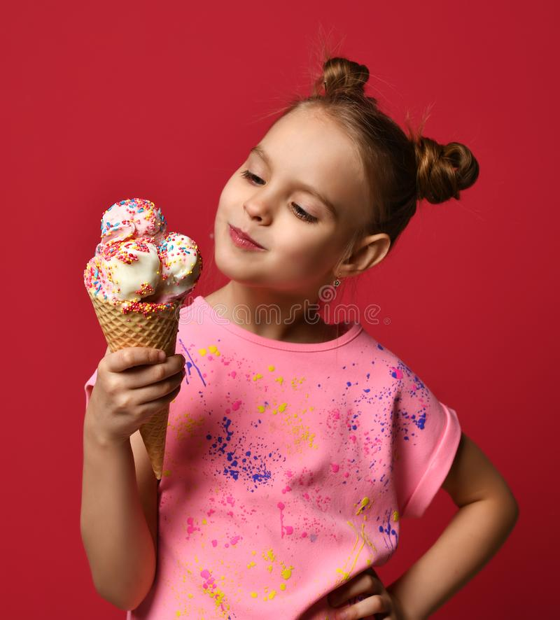 Baby girl kid hold big ice cream in waffles cone with raspberry happy smiling ready to eat on red background stock photography