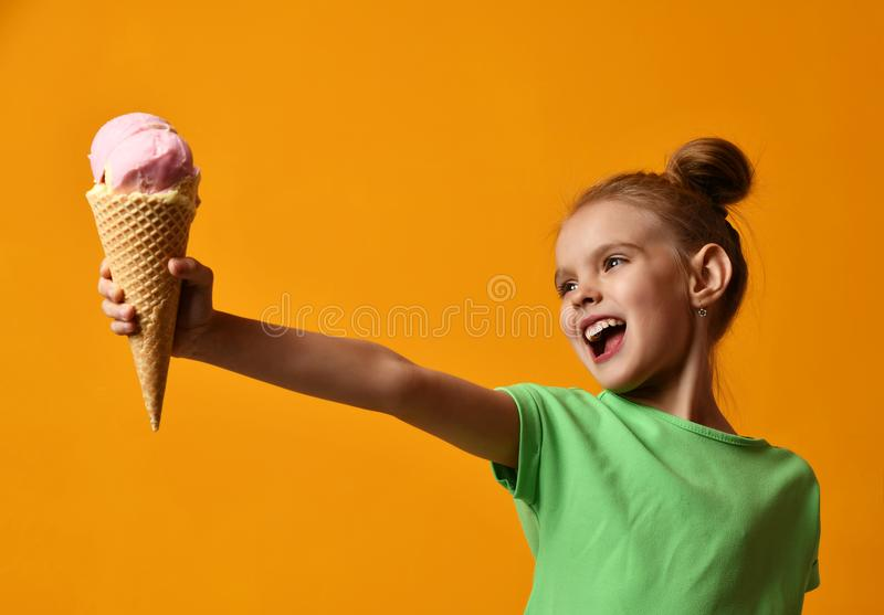 Pretty baby girl kid hold strawberry ice cream in waffles cone stock images