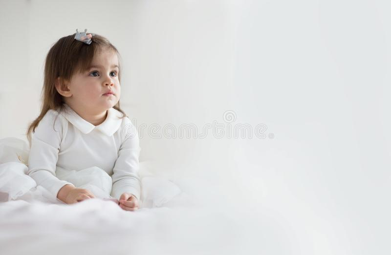 Pretty baby girl in white dress stock photo