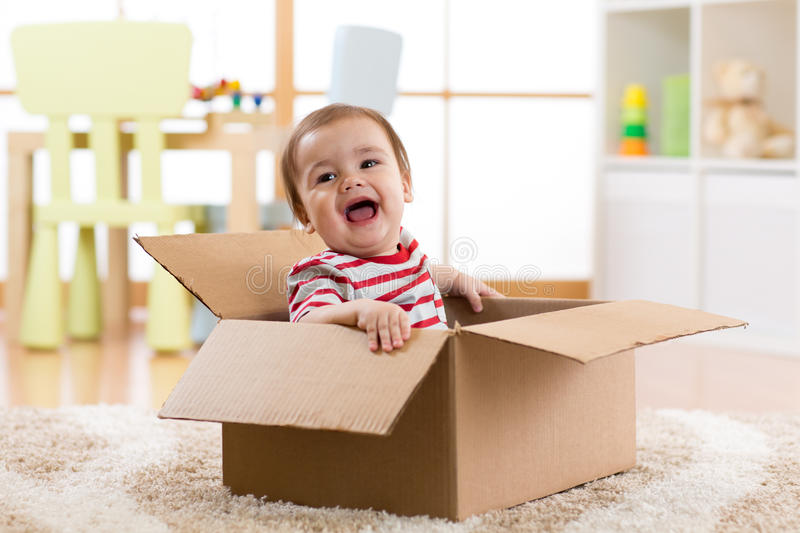 Pretty baby infant boy sitting inside box royalty free stock images