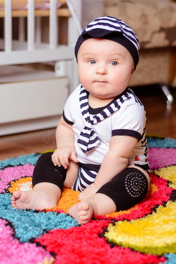 A pretty baby in a striped shirt and hats seated on the mat in the room stock photo