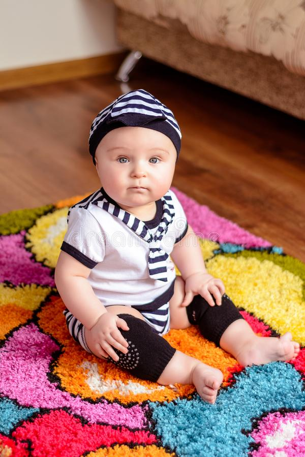 A pretty baby in a striped shirt and hats seated on the mat in the room stock photography