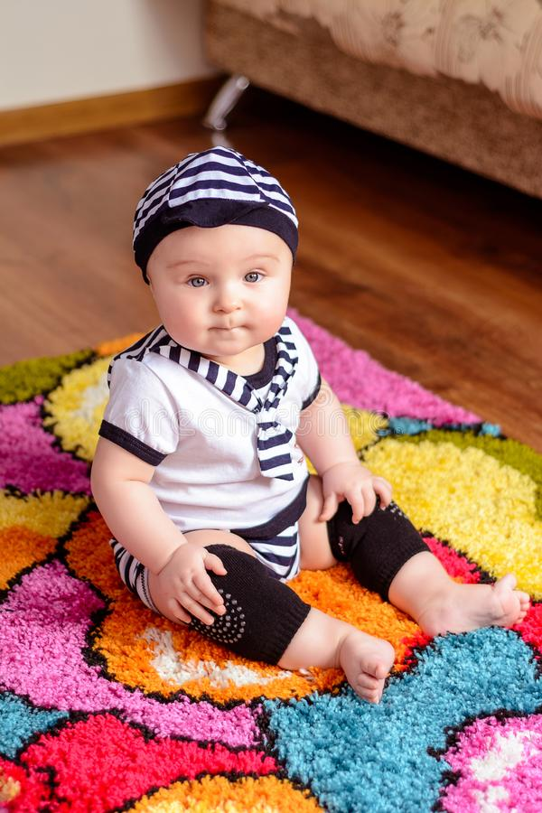 A pretty baby in a striped shirt and hats seated on the mat in the room royalty free stock images