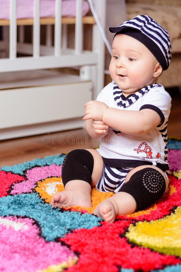 A pretty baby in a striped shirt and hats seated on the mat in the room royalty free stock image