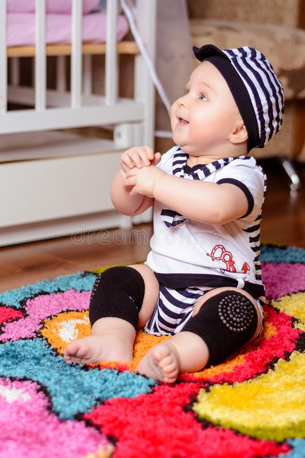 A pretty baby in a striped shirt and hats seated on the mat in the room stock photos