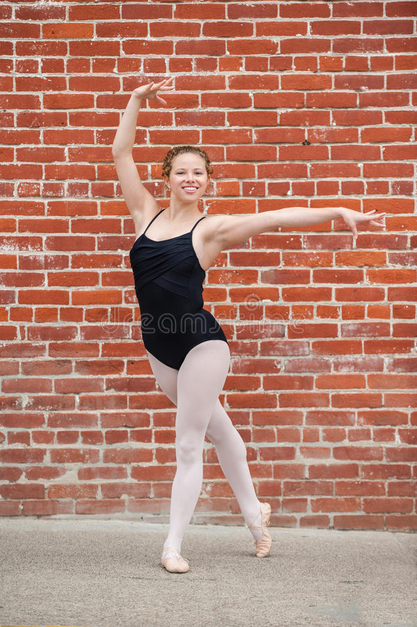 Pretty ballet girl posed in front of red brick wall. Beautiful and young ballerina gracefully posed in Ecarte while facing forward stock photos