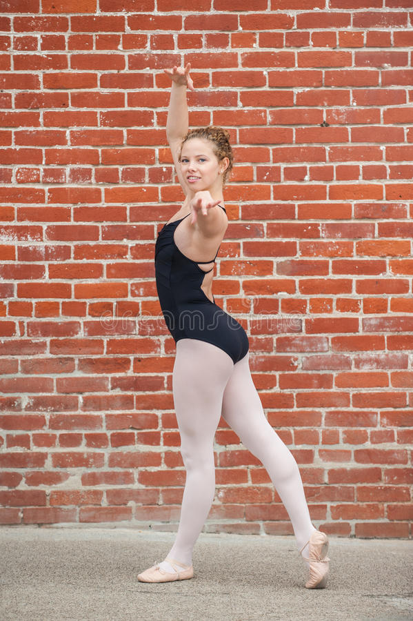 Pretty ballet girl posed in front of red brick wall. Beautiful and young ballerina gracefully posed in Ecarte while facing left stock photography