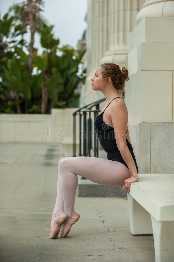 Pretty ballet girl posed on white bench. Beautiful and young ballerina looking ahead while seated with toes pointed stock photos