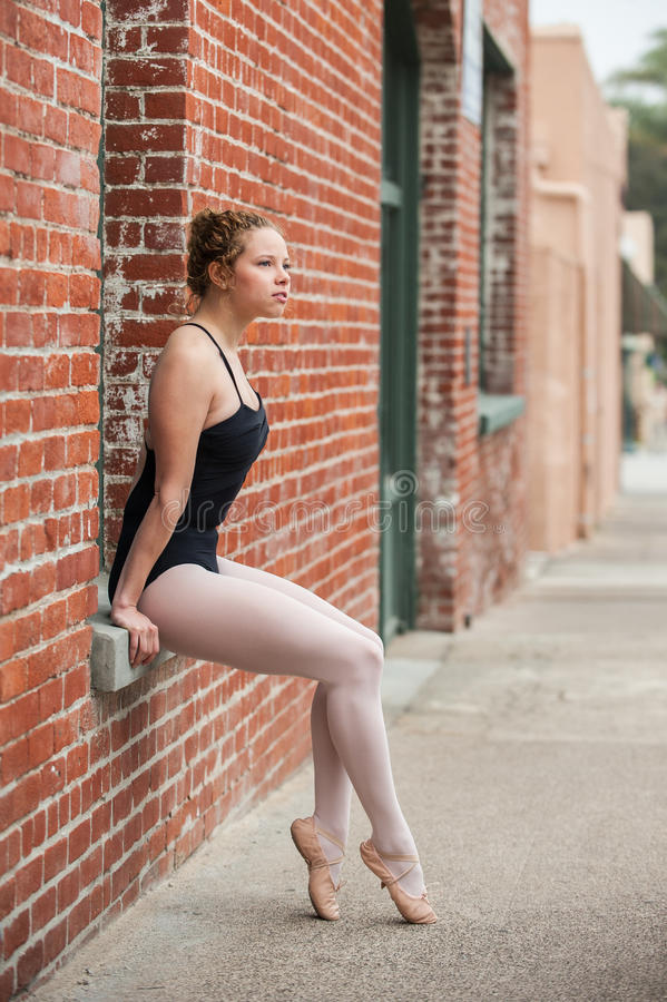 Pretty ballet girl posed on window seat. Youthful ballerina seated in red brick window sill while looking off to distance stock image