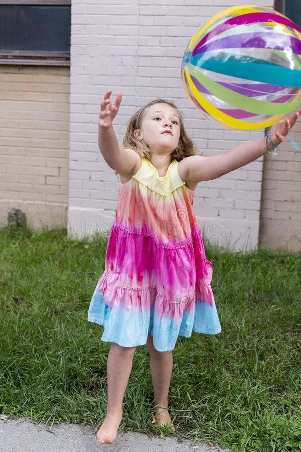 Vertical frontal photo of little girl in rainbow coloured summer dress throwing multicolored beach ball. Pretty barefoot little girl in rainbow coloured summer royalty free stock photography