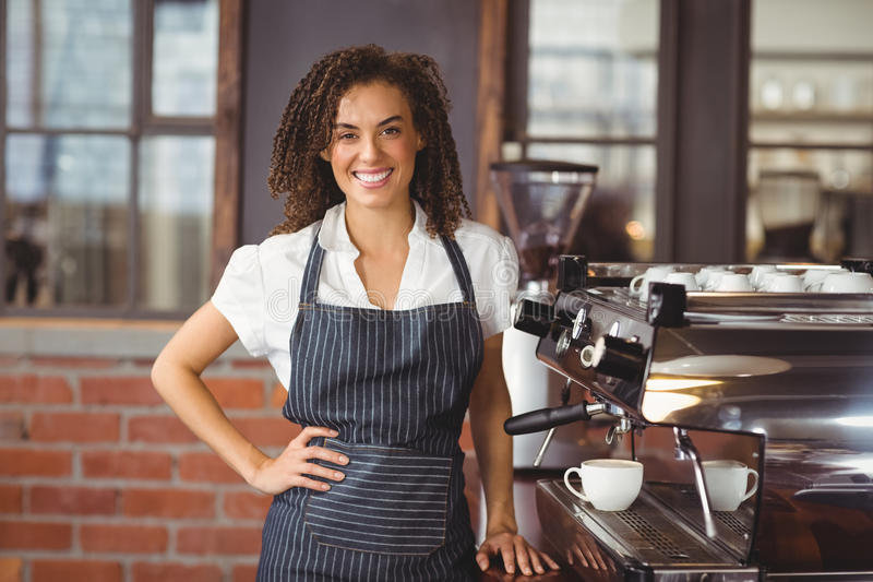 Pretty barista smiling next to coffee machine royalty free stock photography