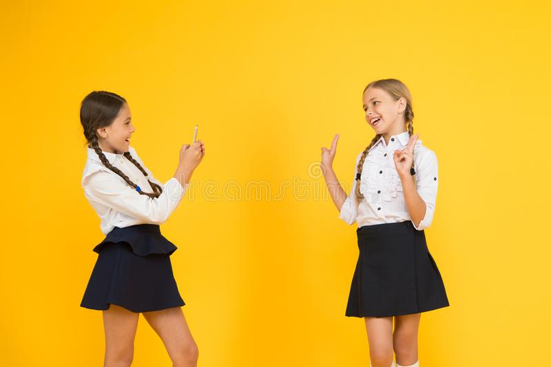 Pretty beauties. small girls in school uniform. back to school. educational blog. new technology. online education. Knowledge day. happy pupils with smartphone royalty free stock photos