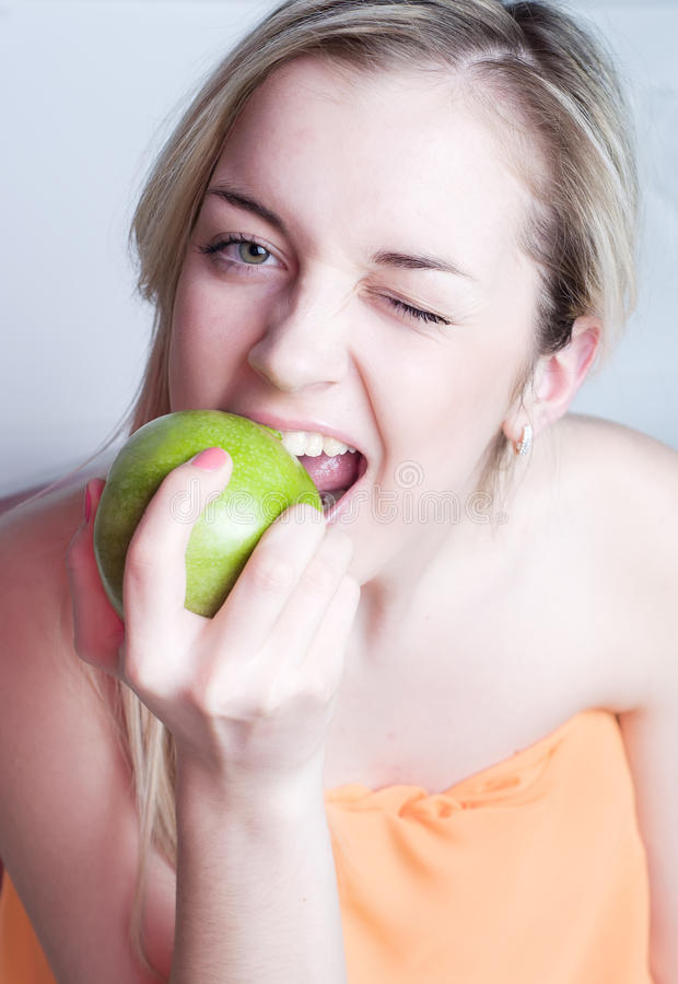Pretty beautiful blond woman with apple royalty free stock image