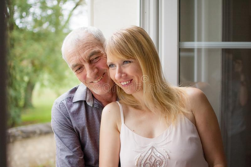 Pretty Beautiful Blonde Standing near the Window with Her Senior Husband and Smiling. Age Difference Concept. stock image