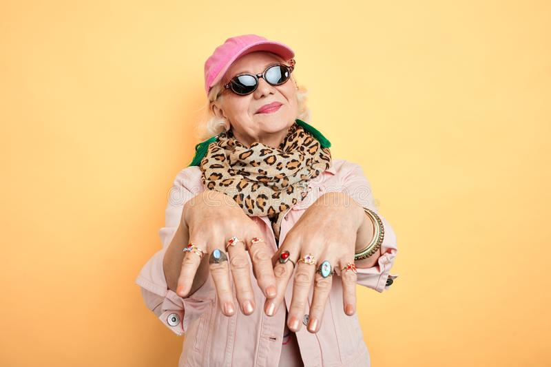 Pretty beautiful fashion old lady boasting about her rings royalty free stock photo