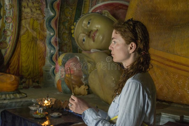 Pretty beautiful girl holding burning sticks of incense at the holy buddhist temple stock image