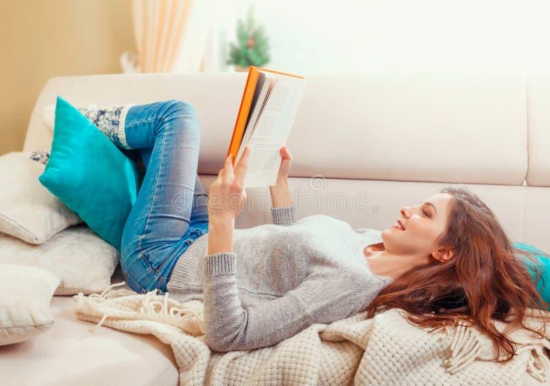 Pretty beautiful girl reading a book at sofa royalty free stock photos