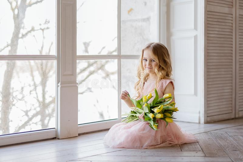 Pretty beautiful girl sitting on the floor with yellow flowers tulips and smiling. Indoor photo. Nice girl. Copy space. Pretty beautiful girl sitting on the royalty free stock photography