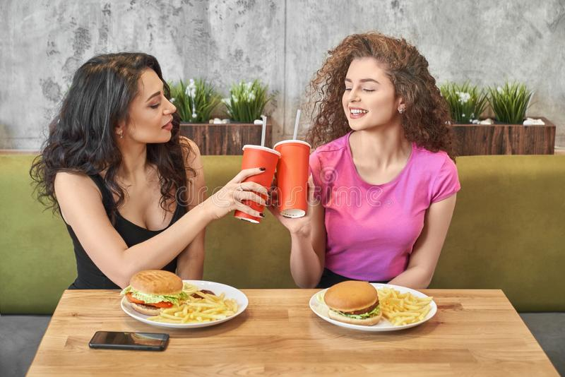 Pretty girls sitting in cafe and clinking paper cups. stock photos