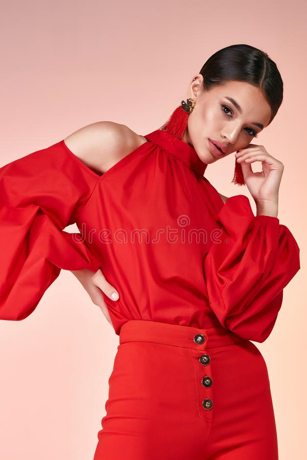 Pretty beautiful elegance woman fashion model glamor pose w. Ear red color trousers silk blouse clothes for party summer collection makeup hair style brunette stock image