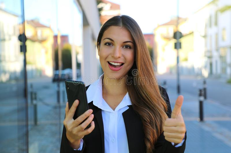 Pretty beautiful young business woman holding smart phone gives thumb up in the street royalty free stock photos