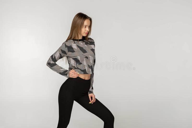 Pretty beautiful young woman in black sportswear with long hair stock image