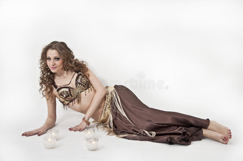 Pretty belly dancer posing on white background