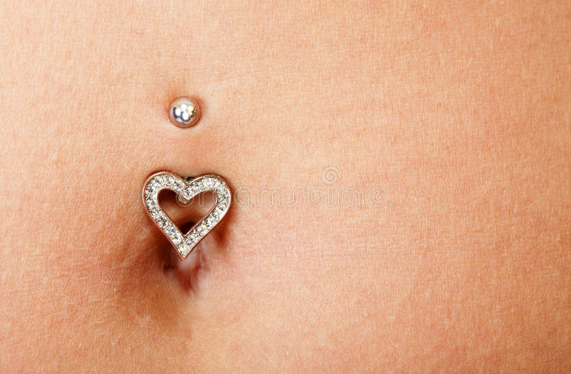 Pretty belly and piercing. Woman's belly with a piercing in the navel royalty free stock photo