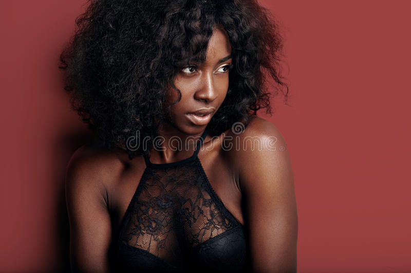 Pretty black woman with ideal skin on a red background royalty free stock image
