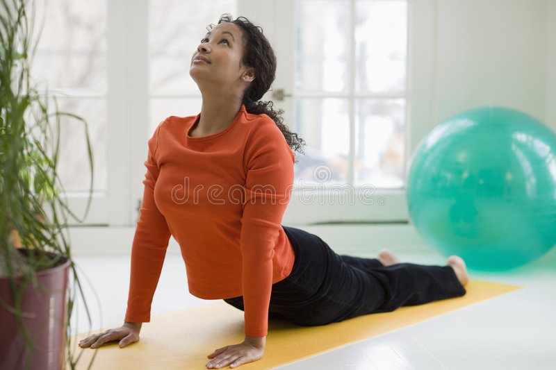 Pretty black woman practicing yoga stock images