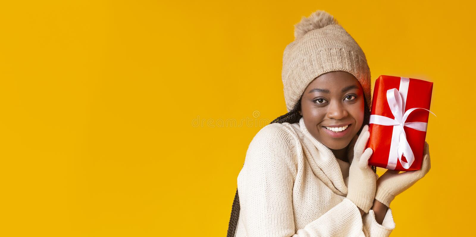 Pretty black woman in winter hat and gloves holding gift stock photography
