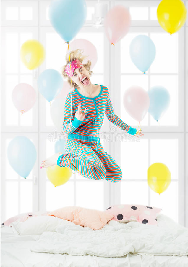 Pretty blond fooling around delight jumping on the bed. Young blonde woman in the Striped Pijamas fooling around delight jumping on the bed, and enjoy life every royalty free stock photos